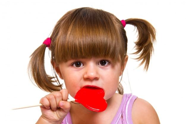 Kleines mädchen, das roten herzlutscher isst Premium Fotos