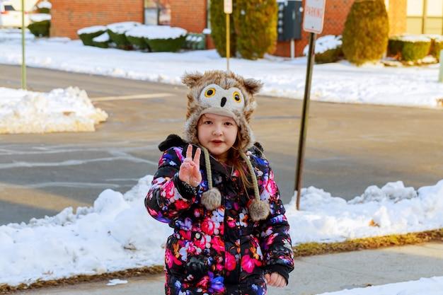 Kleines mädchen, das schnee auf hauptfahrweise schaufelt. schöner schneebedeckter garten oder vorgarten. Premium Fotos