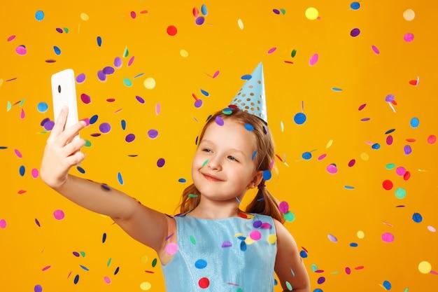 Kleines mädchen, das selfie unter fallenden konfettis macht. Premium Fotos