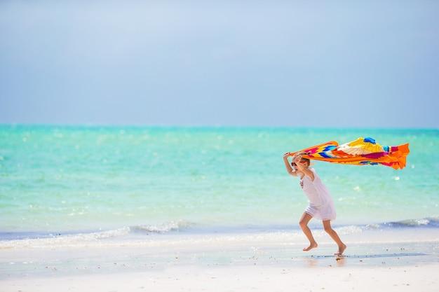 Kleines mädchen, das spaß hat, mit pareo auf tropischem strand zu laufen Premium Fotos