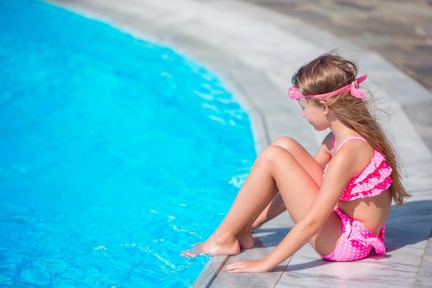 Kleines mädchen, das spaß mit einem spritzen nahe swimmingpool hat Premium Fotos