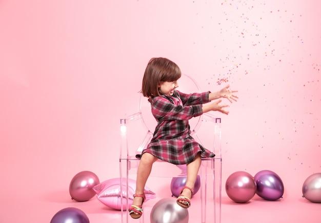 Kleines mädchen, das spaß mit konfetti hat. konzept der feier und des spaßes. Kostenlose Fotos