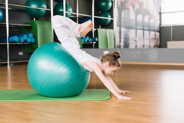Kleines mädchen, das übungen mit dem trainieren des balls in der eignungsturnhalle tut Kostenlose Fotos
