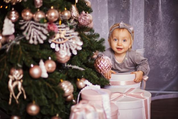 Kleines mädchen, das unter dem weihnachtsbaum sitzt. sie umarmt ihre hände weihnachtsgeschenkboxen Premium Fotos