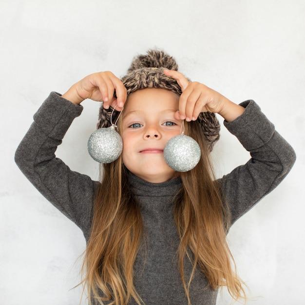 Kleines mädchen, das weihnachtskugeln nah an ihrem gesicht hält Kostenlose Fotos