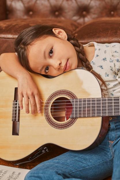Kleines mädchen, das zu hause gitarre spielt Kostenlose Fotos