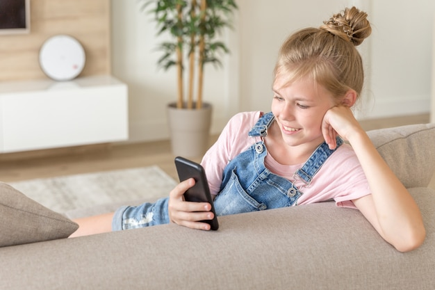 Kleines mädchen, das zu hause mit einem handy auf einer couch spielt Premium Fotos