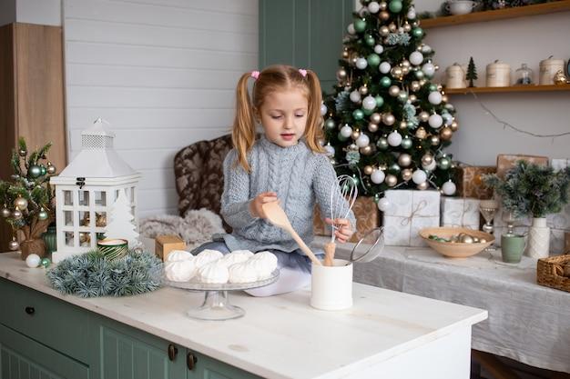 Kleines mädchen, das zu hause weihnachtslebensmittel zubereitet Premium Fotos