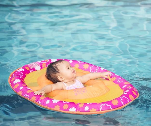 Kleines mädchen der nahaufnahme sitzen in einem boot für kinder im swimmingpoolhintergrund mit kopienraum Premium Fotos