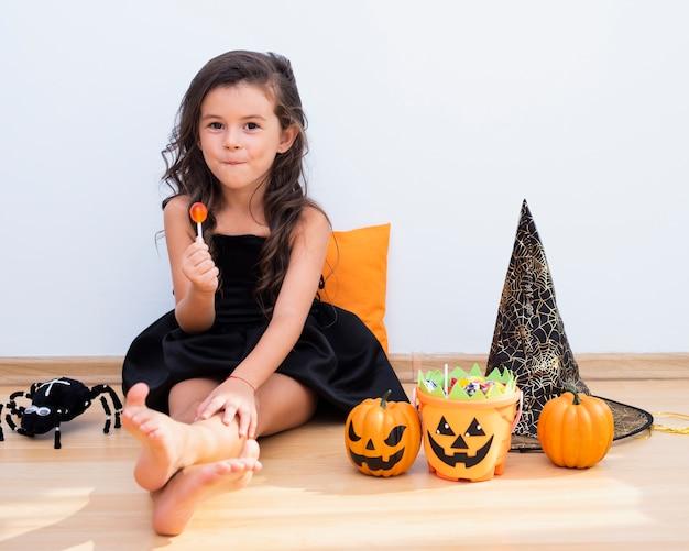Kleines mädchen der vorderansicht, das auf boden auf halloween sitzt Kostenlose Fotos