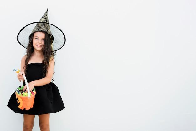 Kleines mädchen der vorderansicht im hexenkostüm für halloween Kostenlose Fotos