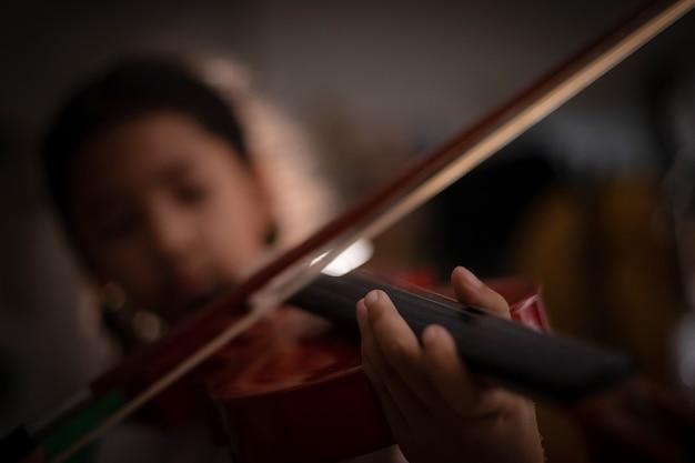 Kleines mädchen des nahaufnahmeschusses, welches das violinenorchester instrumental mit weinleseton und lichteffektdunkelheit spielt und korn verarbeitete flache schärfentiefe des ausgewählten fokus Premium Fotos