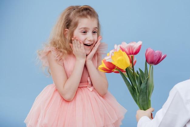 Kleines mädchen erhält blumen, isoliert auf blauer wand, nahaufnahme, zwei kleine kinder. Premium Fotos