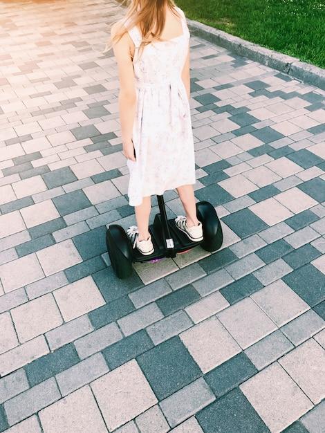 Kleines mädchen fahren auf ein hoverboard im park. rückansicht Premium Fotos