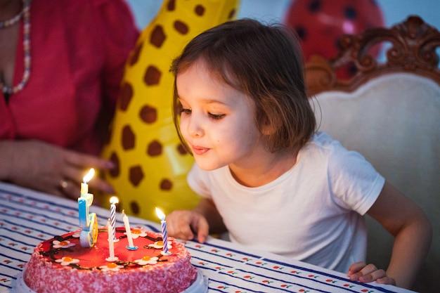 Kleines mädchen, geburtstagskind, das kerzen auf kuchen, geburtstagsfeier mit freunden heraus durchbrennt Premium Fotos