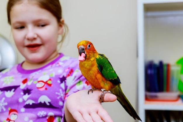 Kleines mädchen hält papageienhände Premium Fotos