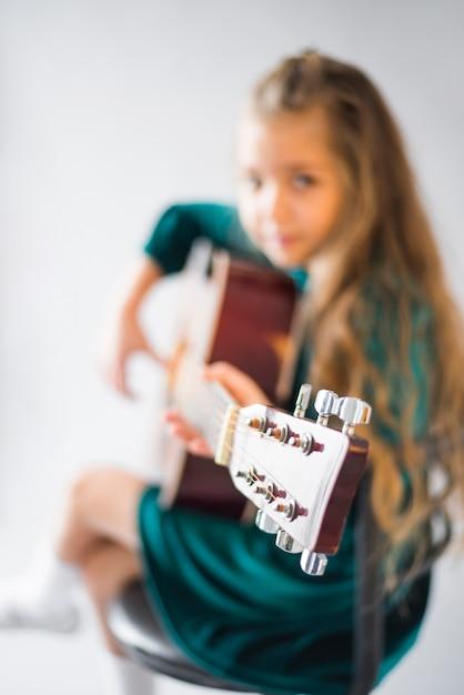 Kleines mädchen im grünen kleid, das akustikgitarre spielt Kostenlose Fotos