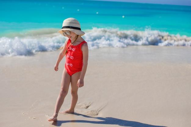 Kleines mädchen im hut am strand während der karibischen ferien Premium Fotos