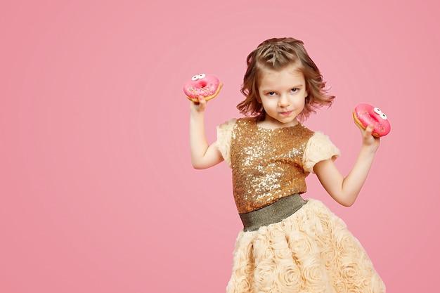 Kleines mädchen im kleid mit donuts Premium Fotos
