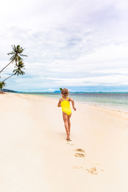 Kleines mädchen im rand in form von weihnachtsbäumen und gelbem badeanzug läuft auf den strand Premium Fotos
