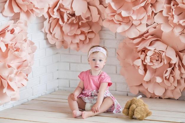Kleines mädchen im rosa kleid sitzt unter großen rosa papierblumen Kostenlose Fotos