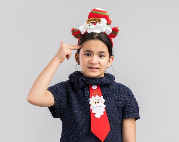 Kleines mädchen im strickkleid trägt rote krawatte mit lustigem weihnachtsrand auf kopf, der genervt pistolengeste mit fingern über kopf macht Kostenlose Fotos