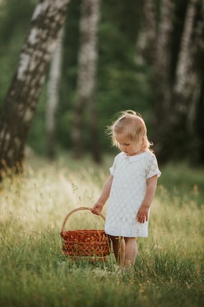 Kleines mädchen im weißen kleid mit korb sonnigen sommertag im wald genießend Premium Fotos