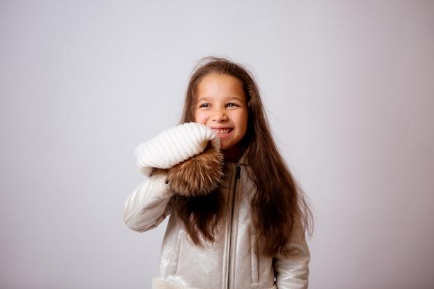 Kleines mädchen im winterhut lächelnd auf weiß Premium Fotos