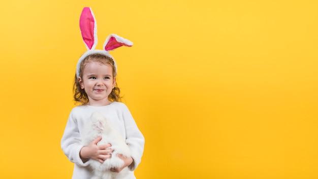 Kleines mädchen in den häschenohren, die mit kaninchen stehen Kostenlose Fotos