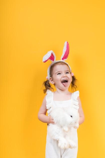Kleines mädchen in den häschenohren mit dem kaninchen, das zunge zeigt Kostenlose Fotos