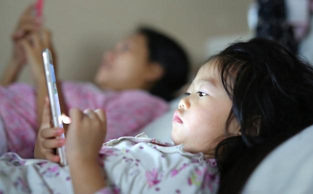 Kleines mädchen in den pyjamas mit der mutter, die den smartphone liegt auf einem bett spielt Premium Fotos