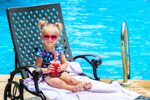 Kleines mädchen in der badebekleidung und in sonnenbrille, die auf ruhesessel im swimmingpool liegen. Premium Fotos