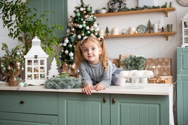 Kleines mädchen in der küche am weihnachtshaus. Premium Fotos