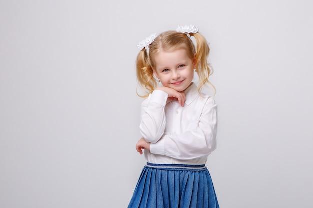 Kleines mädchen in der schuluniform auf weißem hintergrund ein buch lesend Premium Fotos