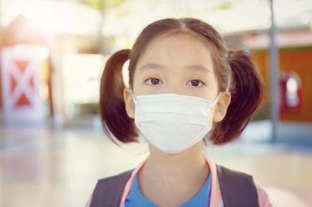 Kleines mädchen in der schuluniform, die eine chirurgische maske mit unscharfem hintergrund trägt Premium Fotos