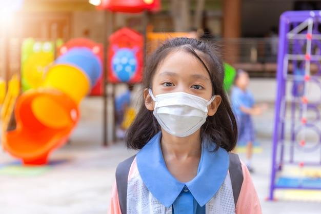 Kleines mädchen in der schuluniform, die eine chirurgische maske mit unscharfem spielplatzhintergrund trägt Premium Fotos