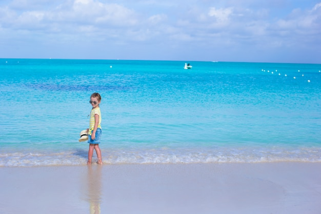 Kleines mädchen in der sonnenbrille am strand während der sommerferien Premium Fotos