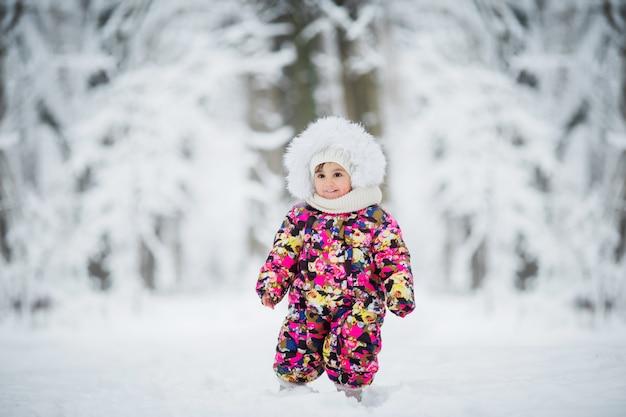 Kleines mädchen in der winterkleidung, die im schnee spielt Premium Fotos