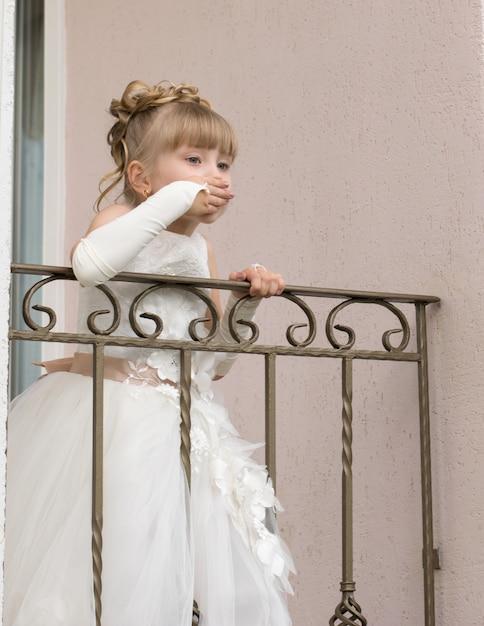 Kleines mädchen in einem ballkleid auf dem balkon Premium Fotos