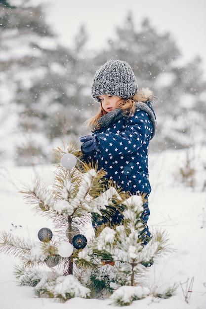 Kleines mädchen in einem blauen hut, der in einem winterwald spielt Kostenlose Fotos