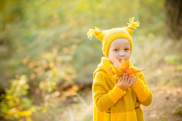 Kleines mädchen in einem gelben strickmantel und in einem hut im herbstpark. Premium Fotos