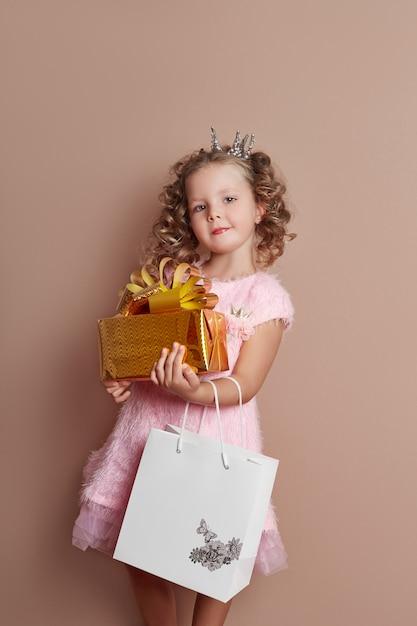 Kleines mädchen in einem rosa kleid hält eine goldene geschenkbox Premium Fotos