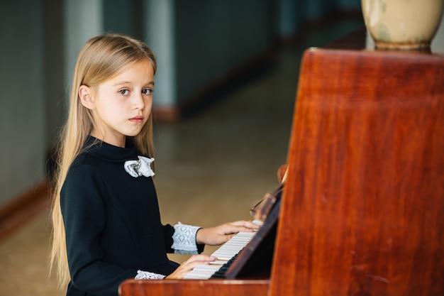 Kleines mädchen in einem schwarzen kleid lernt, klavier zu spielen. das kind spielt ein musikinstrument. Premium Fotos