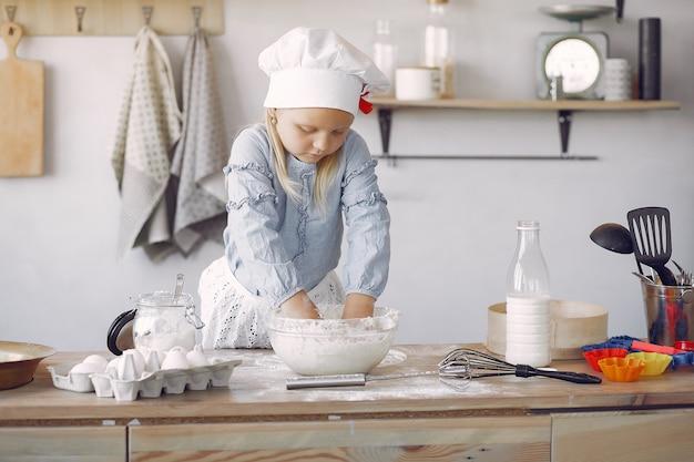 Kleines mädchen in einem weißen schafhut kochen den teig für plätzchen Kostenlose Fotos