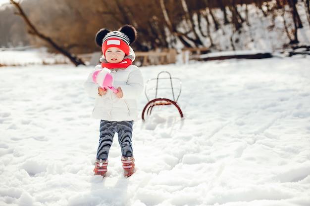 Kleines mädchen in einem winterpark Kostenlose Fotos