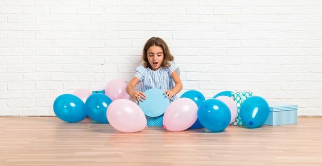 Kleines mädchen in einer geburtstagsfeier, die ein geschenk mit überraschungsgeste öffnet Premium Fotos