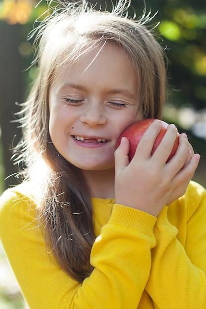 Kleines mädchen in einer gelben jacke steht im park und hält reife granatäpfel. Premium Fotos