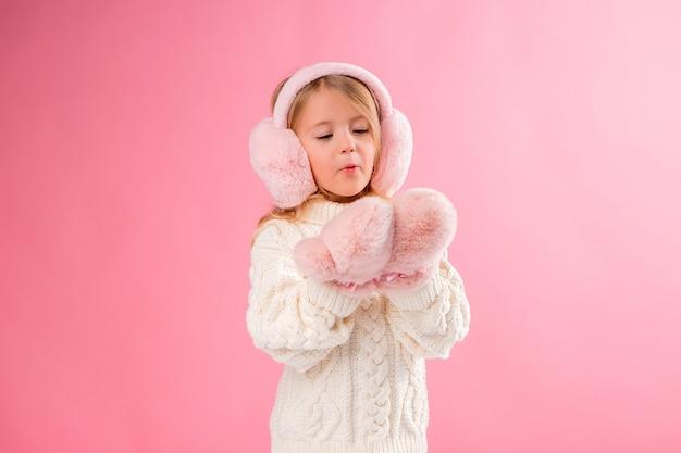Kleines mädchen in rosa fäustlinge und kopfhörer an einer rosa wand Premium Fotos