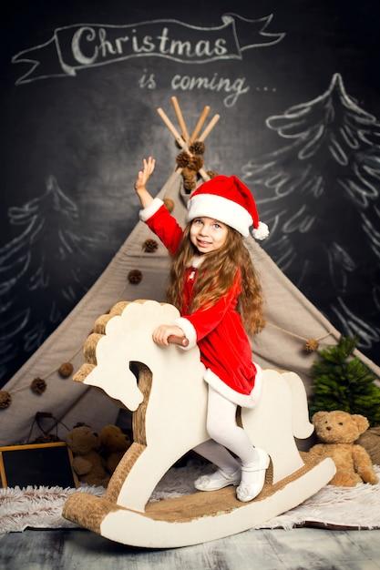Kleines mädchen in santa kostüm auf einem schaukelpferd ist bereit, die feiertage zu feiern. Premium Fotos