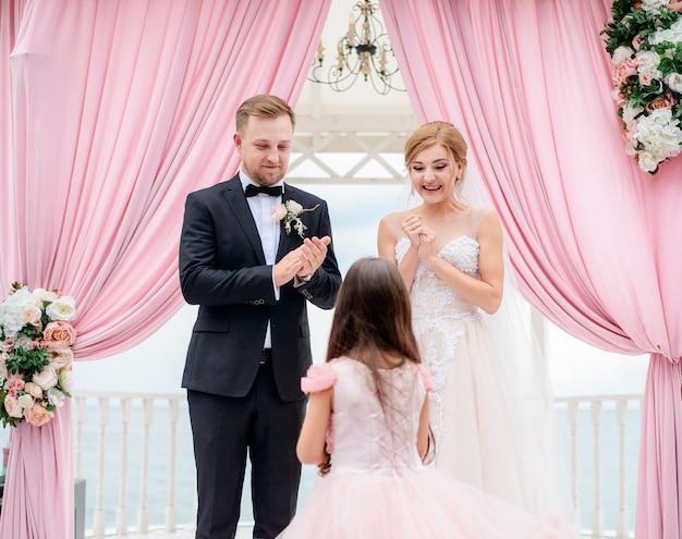 Kleines mädchen kommt zur braut und zum bräutigam mit eheringen während der zeremonie Kostenlose Fotos